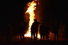 People Standing By Fire On Field At Night