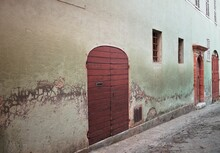 An Old Wooden Door In A Green Wall Of An Old Building (Marche, Italy, Europe)
