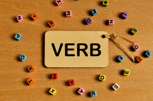 Top View Of Colorful Alphabet Beads And Label Tag Written With VERB. Education Concept.