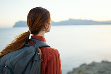 Woman Tourist In An Orange Sweater And With A Backpack On Her Back Is Resting Near The Sea And Mountains In The Distance