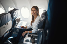 Happy Lady In The Airplane With Modern Devices