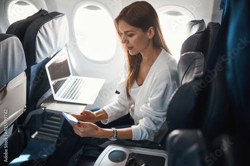 Photo Calm young lady with two modern gadgets in the plane
