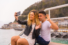 Lifestyle Of A Caucasian Couple Sightseeing On Vacation Sitting By The Sea Taking A Picture Of Themselves
