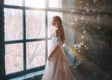 Romantic Lady, Blonde Woman With Long Hair In White Vintage Dress Stands In Dark Room, Looks Out Window. Girl Bride Princess In Wedding Dress. Elegant Hairstyle. Bright Rays Of Sun Concept Of Waiting