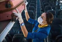 Airline Stewardess Carefully Putting Pink Suitcase Into Luggage Rack