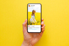 Mobile Phone On Yellow Background With Photo Of Woman In Yellow Meadow On The Screen