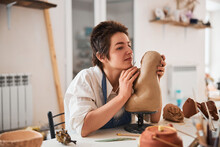 Pottery Master Pulling Clay Statue Closer To Her Face