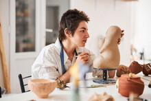 Woman Checking Out Her Pottery Work For Flaws
