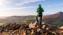 Hiker With A Backpack On A Rocky Mountain Peak Looking In The Distance. Landscape From Little Sugar Loaf Peak In Wicklow Mountains, Ireland.