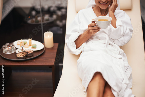 Charming beautiful elegant woman in white bathrobe drinking beverage while spend Fototapet