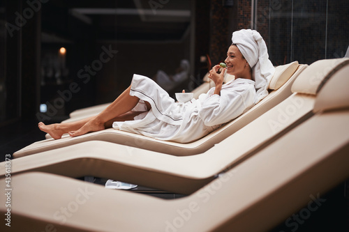 Beautiful charming Caucasian woman with towel on head sitting on deck chair in s Fototapet