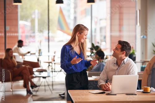 Tela Businessman And Businesswoman Having Informal Meeting By Desk In Modern Open Pla