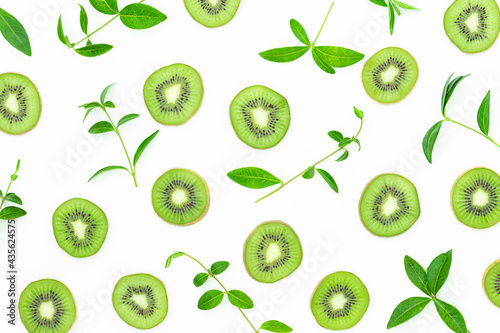 Summer bright background with slices of kiwi and green leaves on the gray surface