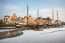 House Facades And Boats Moored In The Frozen Canal Of Spaarne River, Haarlem, Amsterdam District, North Holland, The Netherlands