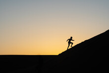 Silhouette Of A Man Running Up A Sand Dune In Nags Head, North Carolina United States Of America