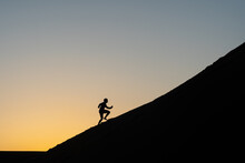 Silhouette Of A Man Running Up A Sand Dune In Nags Head, North Carolina
