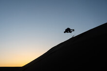 Silhouette Of A Man Tumbling Down A Sand Dune In Nags Head, North Carolina