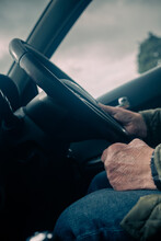 Old Man With One Hand On The Steering Wheel And Another Hand On His Lap While Driving.