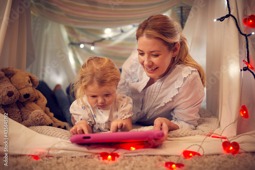 Mother And Young Daughter Looking At Digital Tablet In Homemade Camp In Child's Bedroom At Home