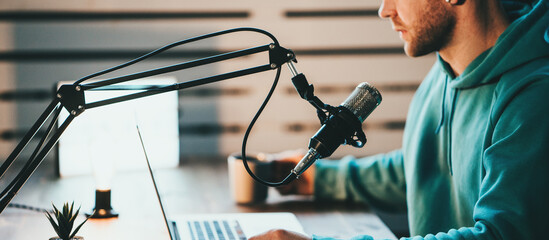 Cheerful host with stubble streaming his audio podcast using microphone and laptop at his small broadcast studio
