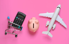 Shopping Still Life. Shopping Trolley, Piggy Bank Airplane Figurine, Calculator On Pink Background. Top View