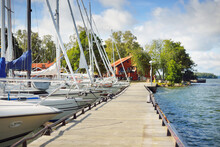 Sailboats Moored To A Pier. Traditional Houses Colored With Falu Red Dye. Summer Vacations, Recreation, Leisure Activity, Service, Private Vessels. Björkö Island, Lake Mälaren, Sweden