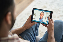 Young Indian Latin Bearded Businessman Having Videocall Videoconference At Home With Black Female Doctor Therapist Using Tablet Computer. Online Virtual Telemedicine Health Care Concept.