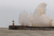 Waves Crash Against The Newhaven Harbour Wall During The Morning High Tide.