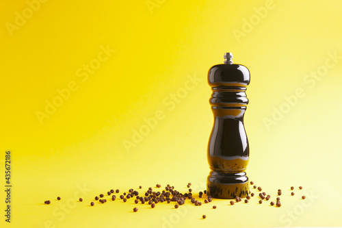Wallpaper Mural Close up view of black pepper mill with peppercorns on yellow background