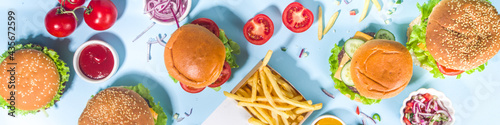 Fastfood, burger party concept. Various delicious burgers set with french fries and sauces on bright blue background flatlay top view copy space