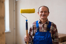 A Happy Old Working Man With A Paint Roller Mustache, Wearing A Blue Uniform And A Plaid Shirt, Looks At The Camera. Home Renovation