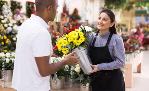 Friendly seller offering gift flower arrangement with roses to male buyer