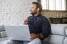 Contemplative Mixed-race Hindu Guy Sits On The Sofa With A Laptop And Waiting For Inspiration, Looks Away, Figured Out How To Solve An Important Problem Or Project Issues