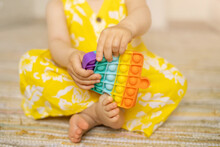 A Little Girl Is Playing With A Modern Pop It Toy. A Fascinating Sensory Toy For The Development . Colorful Popit Toy. Simple Dimple. Baby's Bare Feet Close Up
