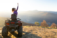 Happy Active Female Driver Enjoying Extreme Riding On ATV Quad Motorbike In Fall Mountains At Sunset.