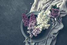 Bouquet Of White And Pink Lilacs On Round Gray Plates And Striped Cotton Shawl On A Dark Surface, Toned, Top View, Copy Space.