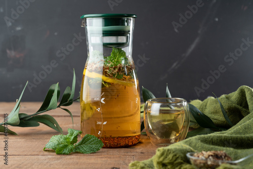 Fotografia, Obraz Preparation of tea with mint leaves and infuser