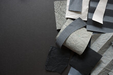 Composition In Textured And 3d Grey Papers Arranged On A Dark Grey Mat Board, With Space For Text - Photographed From Above In A Flat Lay Composition