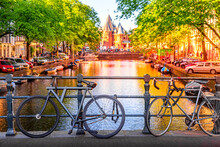 Old Bicycles On The Bridge In Amsterdam, Netherlands Against A Canal And Old Buildings During Summer Sunny Day Sunset. Amsterdam Postcard Iconic View.