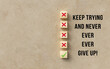 canvas print picture - cubes with several crosses and one checkmark and the message KEEP TRYING AND NEVER EVER EVER GIVE UP! symbolizing trial and error on paper background