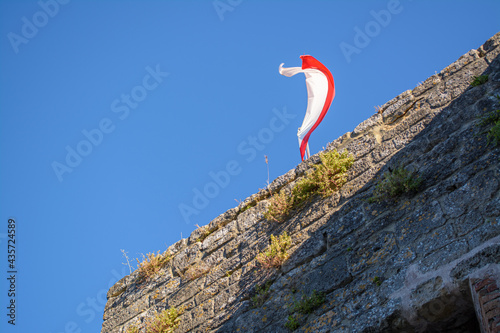 Bandiera al vento sui bastioni della Rocca di Castrocaro, sullo sfondo del cielo Fotobehang