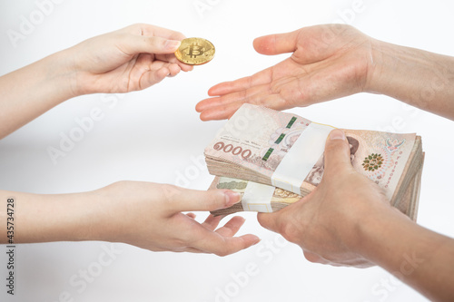 Fotografia, Obraz Cropped shot of people hands trading bitcoin token with Thai baht banknotes isolated on white background
