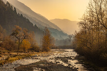 River Flowing Through Misty Mountain Valley Covered With Dense Forests And Mist At Dawn