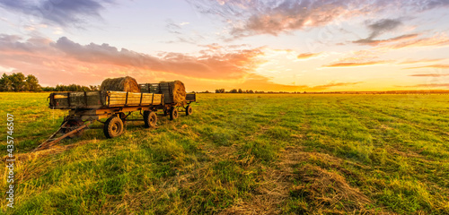 Tablou Canvas Old vintage carriage with hay stacks in green shiny field with beautiful sunset