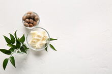 Bowls With Shea Butter And Nuts On Light Background