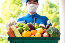 Asian Deliveryman Wearing Face Mask Holding Grocery Basket Outdoors, Hygienic Food Delivery Service In The Time Of Pandemic Concept