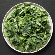 Raw Organic Baby Kale On A Gray Plate On A Black Background, Top View. Flat Lay, Overhead, From Above.