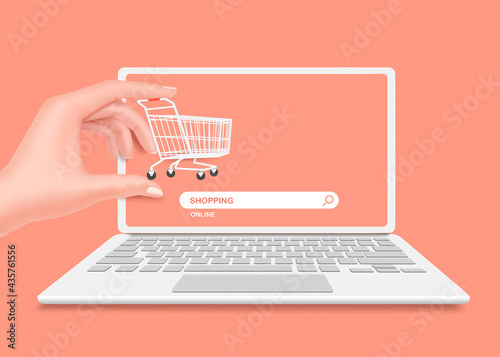 Canvas Hand holding a shopping cart in front of a laptop computer or notebook computer