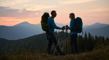 Full Length Of Smiling Man And Woman Travelers Hiking Together In Mountains. Silhouette Of Happy Young Couple With Backpacks Standing On Grassy Hill With Sunset And Grassy Hills On Background.