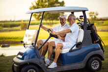 Two Older Friends Are Riding In A Golf Cart.